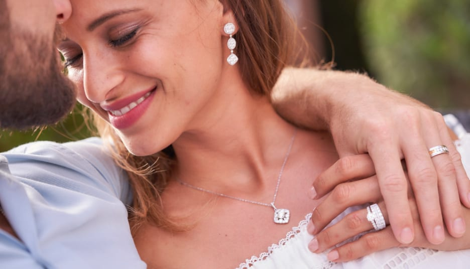 Woman wearing diamond earrings, necklace and ring