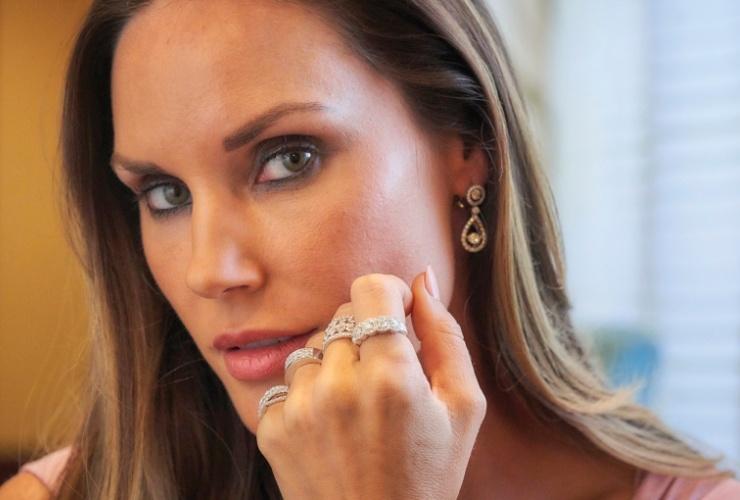 Woman wearing diamond earrings and rings