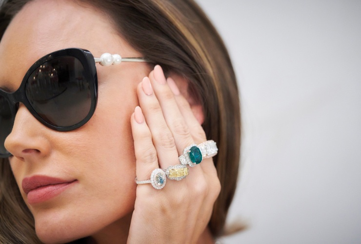 Woman wearing sunglasses and various rings